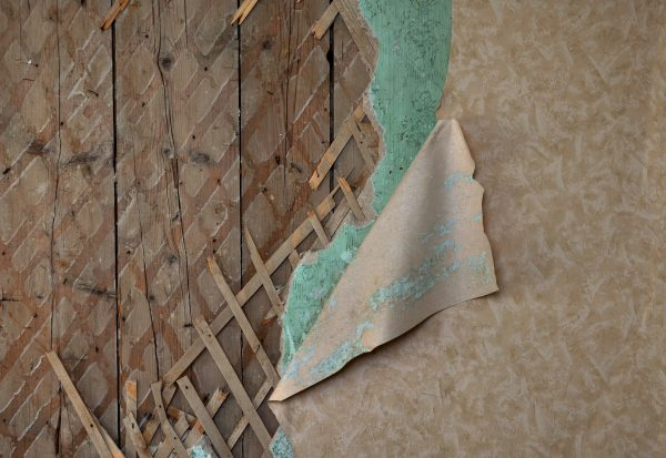Fragment of old destroyed wall with jagged wallpaper and lath in abandoned house
